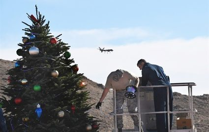 Two men decorating a Christmas Tree