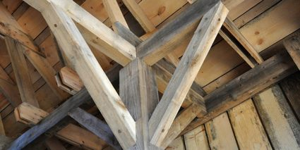 Image of a wooden post and beam construction with diagonal knee bracing supports for each beam.