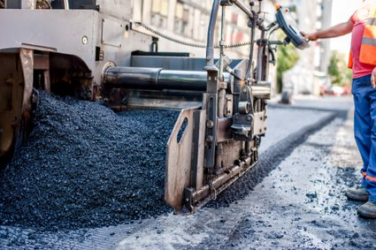 Asphalt pavement being installed showing loose aggregates in the foreground and slightly compressed asphalt in the background
