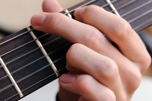 An image of a guitar fingerboard with a hand fretting the strings