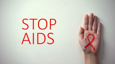 a STOP AIDS campaign poster, showing a hand with a red ribbon - sign of HIV/AIDS