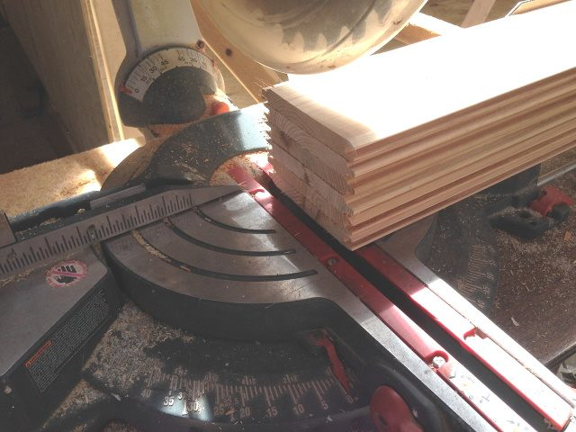 Image of a miter saw with angle set to 0° to make perpendicular cut to multiple boards .