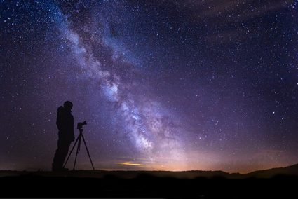 Image of  a scenery showing the Milky Way galaxy arm and a silhouette of a human and a camera on tripod.