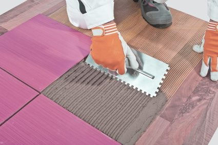 Image of a tile installer applying thinset onto the floor using a notched trowel that leaves a uniform thickness thinset beads on the floor.