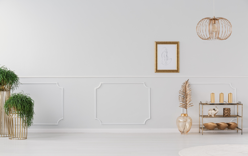 A white wall with wainscoting that gives character to the wall
